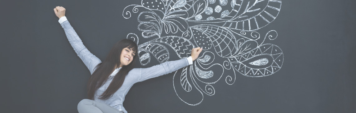 happy-female-teacher-lying-on-blackboard-with-floral-chalk-drawing